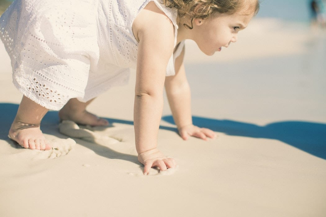 Petite fille s'aidant de ses mains pour se lever